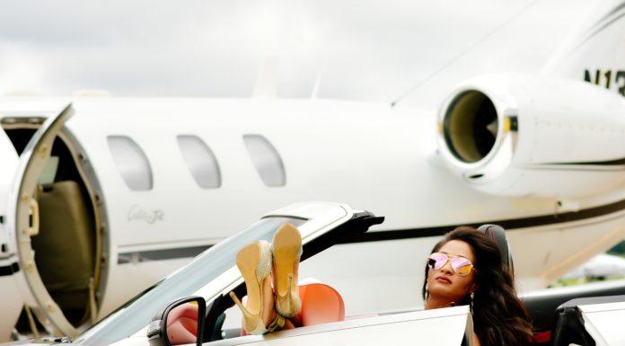 donna su macchina di lusso davanti aereo privato